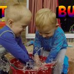 Funny kids playing in garden with water