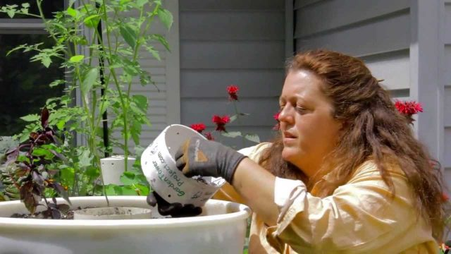Kristi Composting with her vegetable and herb Garden Tower!