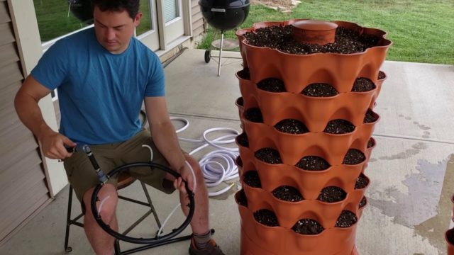 Installing the Garden Tower 2 Watering System: Top-hose configuration in a Garden Tower with soil