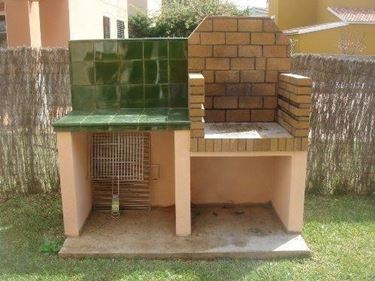 Barbecue in refractory bricks and support surface with tiled wall